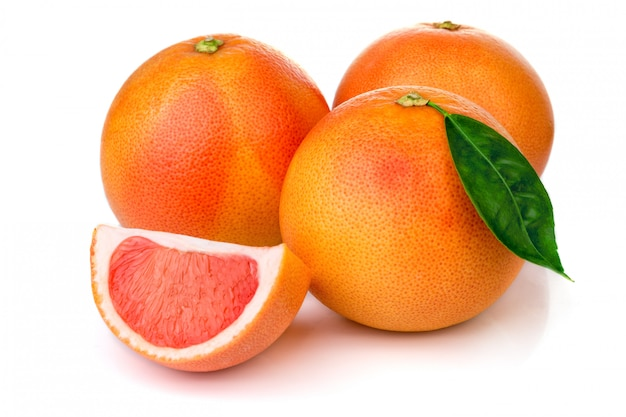 Pink grapefruits with green leaves isolated on white