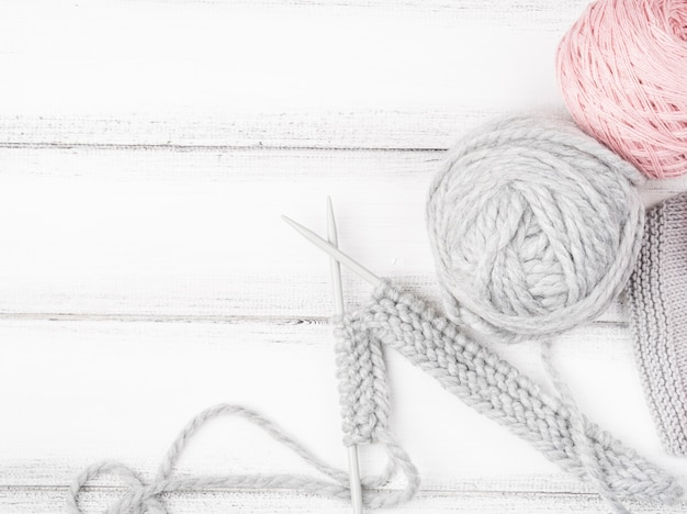 Pink and gray yarn on wood background