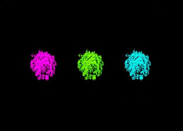 검은 배경에 행으로 배열 된 핑크, 녹색 및 청록색 holi 색상