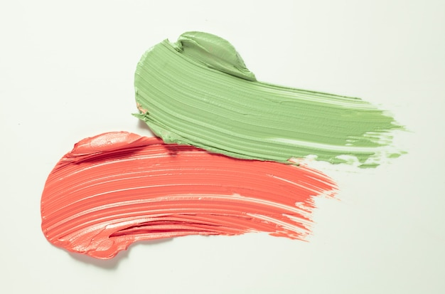 Pink and green concealer foundation corrector gray background