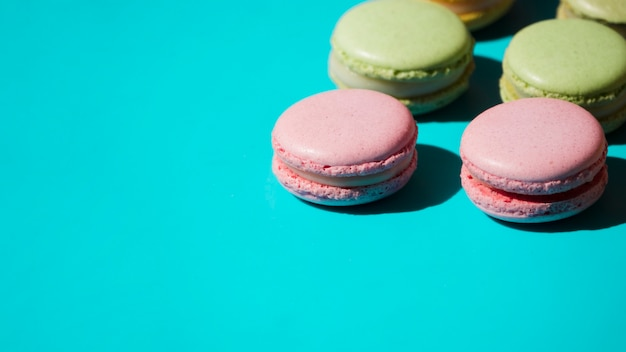 Pink and green macaroons on turquoise backdrop