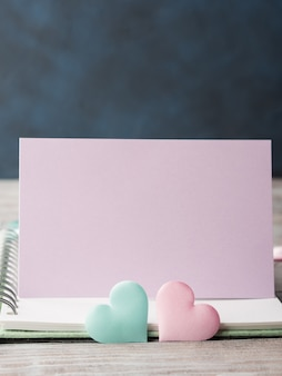 Pink and green pastel hearts on blank card with copyspace
