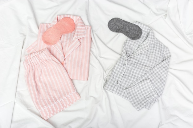 Pink and grey pajamas for two people, and sleep mask for eye on white cotton bedsheet.