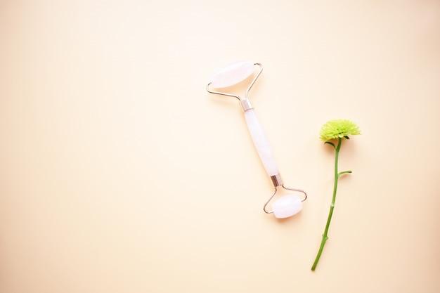 핑크 구아 샤 페이셜 마사지 도구. 로즈 쿼츠 옥 롤러. 집에서 노화 방지, 리프팅 및 토닝 치료. 공간을 복사하십시오. 평면도. 평평하다.