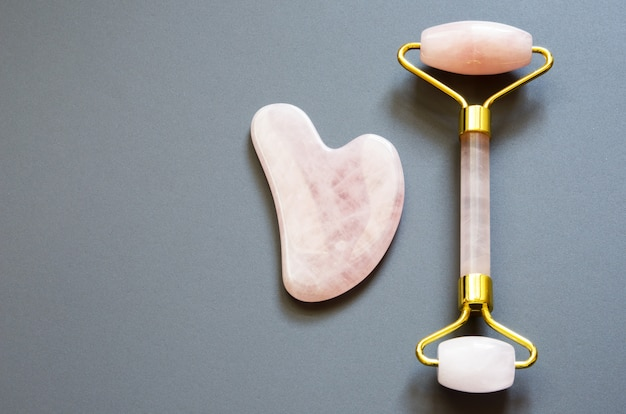 Pink gua sha massage tool. rose quartz roller. facial skin care at home, anti-aging and lifting therapy. top view.