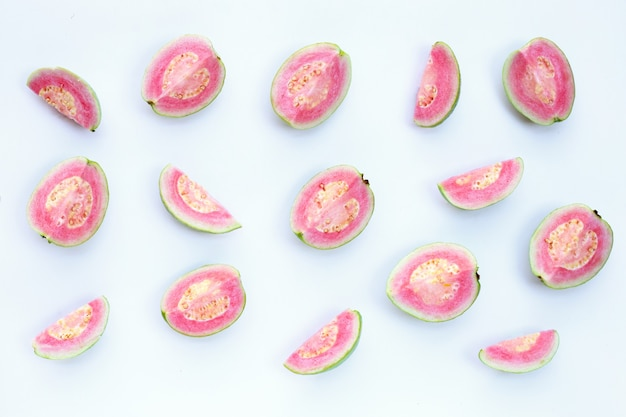 Pink guavas on white surface