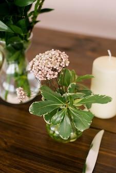 분홍색 석고 꽃과 꽃병에 잎이 있는 녹색 가지. 가정 장식