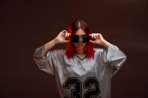 Девушка с розовыми волосами в авангардном стиле в солнечных очках.