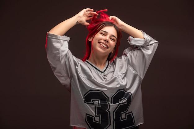 Девушка с розовыми волосами в спортивной одежде с удовольствием.