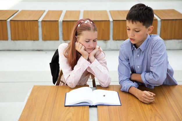 Девушка-подросток с розовыми волосами читает книгу, мальчик-школьник принес ей жука, концепция отношений подростков