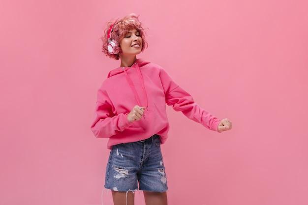 ヘッドフォンでピンクの髪の巻き毛の女性が踊り、音楽を聴きます