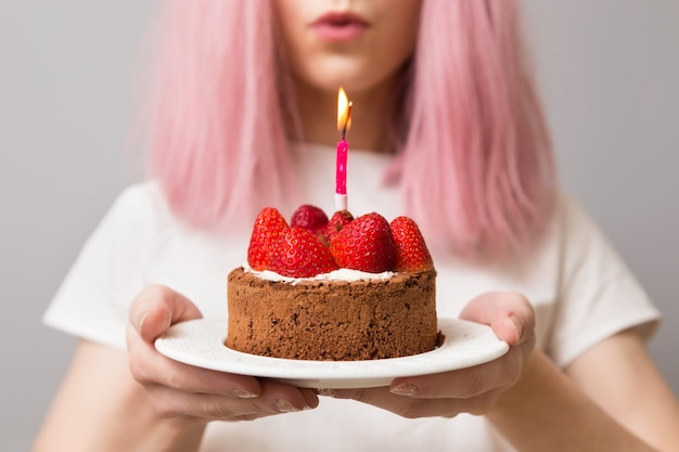 The pink-haired girl is holding birthday  strawberry cake with a candle.