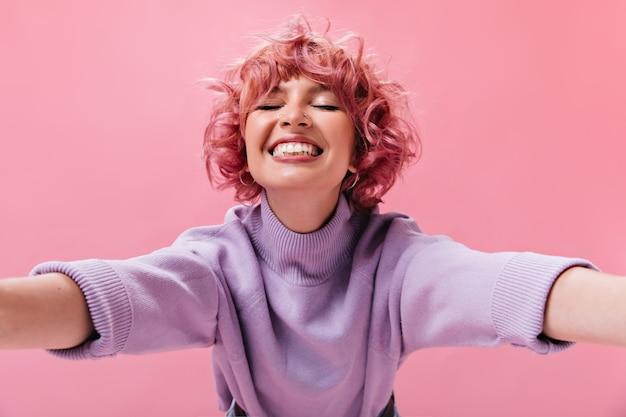 보라색 스웨터를 입은 분홍색 머리의 행복한 매력적인 여성은 외진 곳에 활짝 웃고 있다