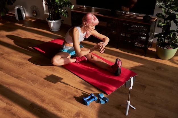 ピンクの髪の女性は、床でのトレーニングでスマートウォッチの時間をチェックします