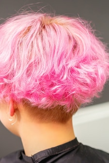 Pink hairstyle of young woman after coloring hair with highlights in beauty salon