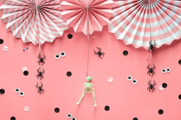 Розовые украшения для хэллоуина. декоративные бумажные вееры, пауки, скелет. черно-белое конфетти.