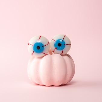 ピンクの眼球とピンクのハロウィーンのカボチャ