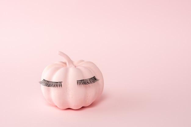 ピンクのまつ毛とピンクのハロウィーンのカボチャ
