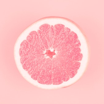 Pink halved fresh juicy grapefruit on pink background