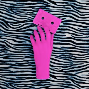 ピンクの手とピンクのオーディオカセット。ゼブラアニマルプリント。ミニマルアート