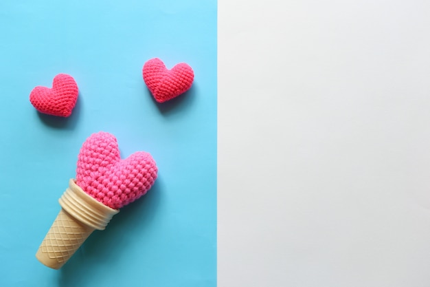Pink handmade crochet heart in waffle cup on colorful background for valentines day