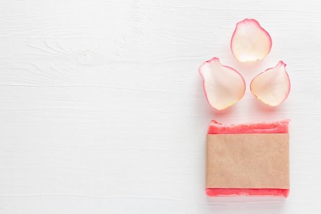 Розовое цветочное мыло ручной работы в пустой бумажной этикетке рядом с лепестками роз на белом