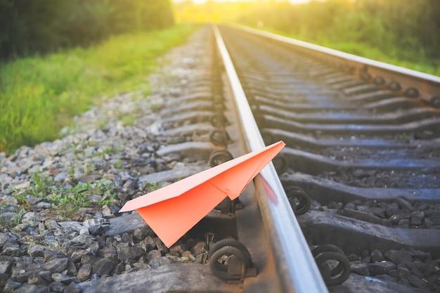 Розовый бумажный самолетик ручной работы, лежащий на рельсовых путях. фото концепции свободы. мотивация образа жизни путешествия. отрасль железнодорожного транспорта.