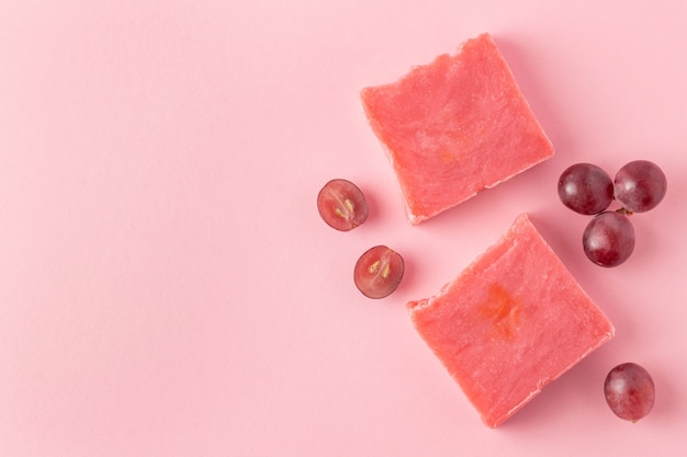 Pink handmade soap and halves cut red grapes on pink background