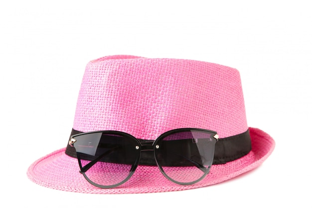 Pink hat and sunglasses isolated .