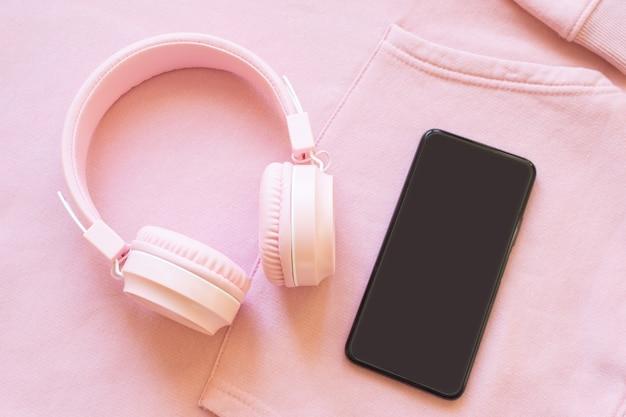 분홍색 배경에 분홍색 헤드폰과 스마트폰. 음악, 팟캐스트, 오디오북에 대한 개념입니다. 상위 뷰, 복사 공간입니다.