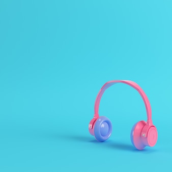 Pink headphones on bright blue background