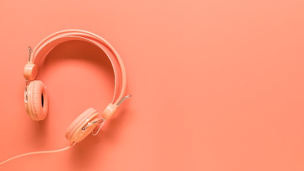 Pink headphones on colored surface
