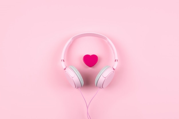 Pink headphones and heart on pink background