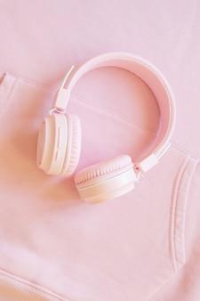 분홍색 배경에 분홍색 헤드폰입니다. 음악, 팟캐스트, 오디오북에 대한 개념입니다. 상위 뷰, 복사 공간입니다.