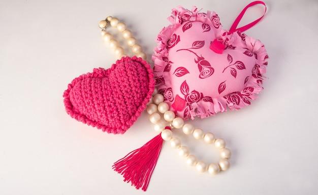 Розовое сердце и жемчужное ожерелье на белой поверхности, выборочный фокус.