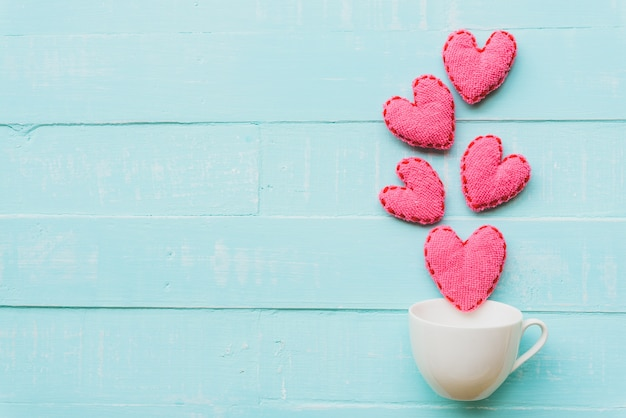 Pink heart on blue and white color wooden background