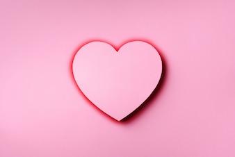 Розовое сердце cutted от бумаги над пробивной пастельной предпосылкой с космосом экземпляра.