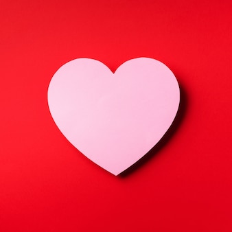 Розовое сердце вырезанные из бумаги на красном фоне с копией пространства.