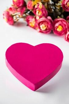 花を背景にバレンタインデーのピンクのハート。クローズアップピンクのハートと白い背景の花の花束。テキスト、垂直写真の場所。