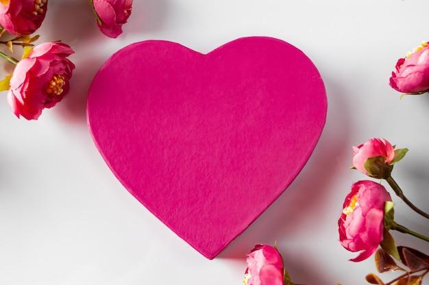 花を背景にバレンタインデーのピンクのハート。ピンクのハート型のギフトボックスと花のフレーム。バレンタインデーのデザイン、テキストの場所。