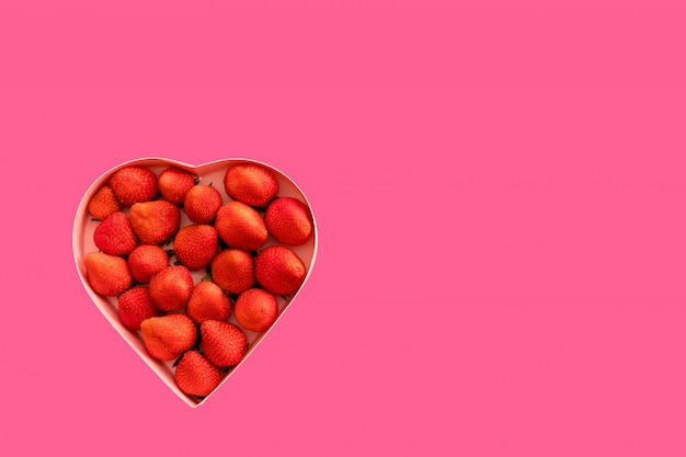 Pink heart gift box with strawberries for valentine's day on a pink background.