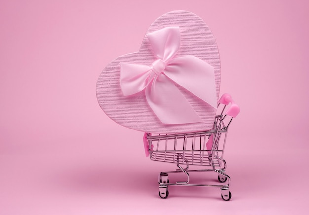 Pink heart gift with bow for valentine's day in shopping scart on a pink background, delivery gift