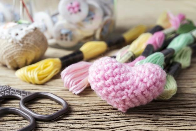 오래 된 나무 테이블에 자 수 핑크 하트 뜨개질 양모와 바느질 스레드
