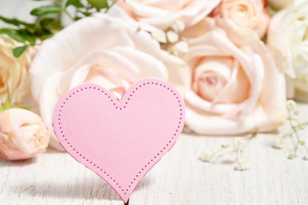 美しいベージュのバラを背景にピンクのハート。