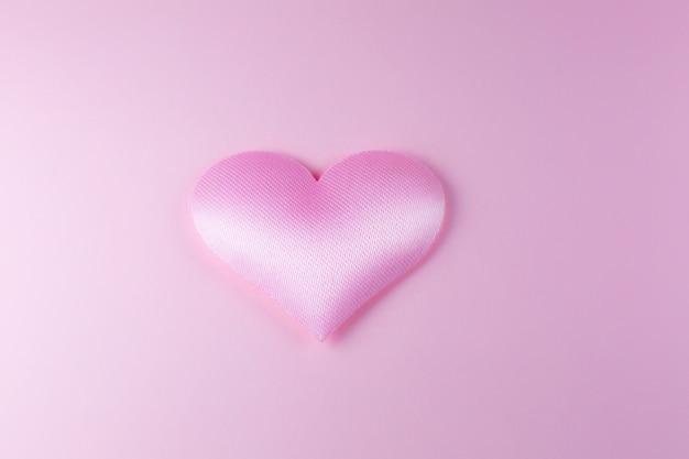 Розовое сердце на розовом фоне. концепция дня святого валентина. любовное и романтическое фото. открытка к празднику. красивые теплые обои с любовью. мягкий фокус. скопируйте пространство.