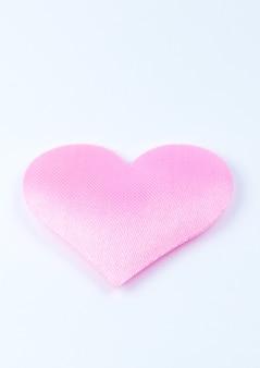 白い背景の上のピンクのハート。聖バレンタインデーのコンセプト。愛とロマンチックな写真。休日のはがき。愛を込めて美しい暖かい壁紙。ソフトフォーカス。スペースをコピーします。