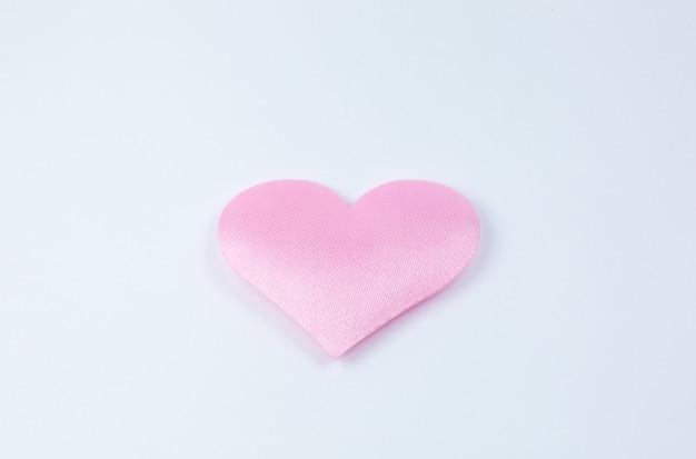 Розовое сердце на белом фоне. концепция дня святого валентина. любовное и романтическое фото. открытка к празднику. красивые теплые обои с любовью. мягкий фокус. скопируйте пространство.