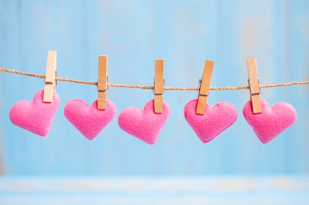 Pink heart shape decoration hanging on line with copy space for text on blue wooden background. love, wedding, romantic and happy valentine' s day holiday concept