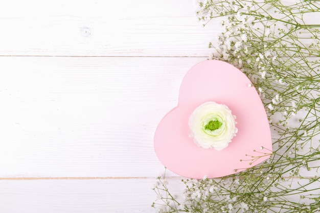 Pink heart shape gift box on a white backround with small withe flowers, celebration valentine's day