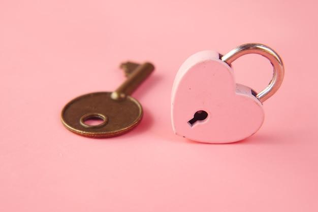 Замок в форме розового сердца и ключ на столе